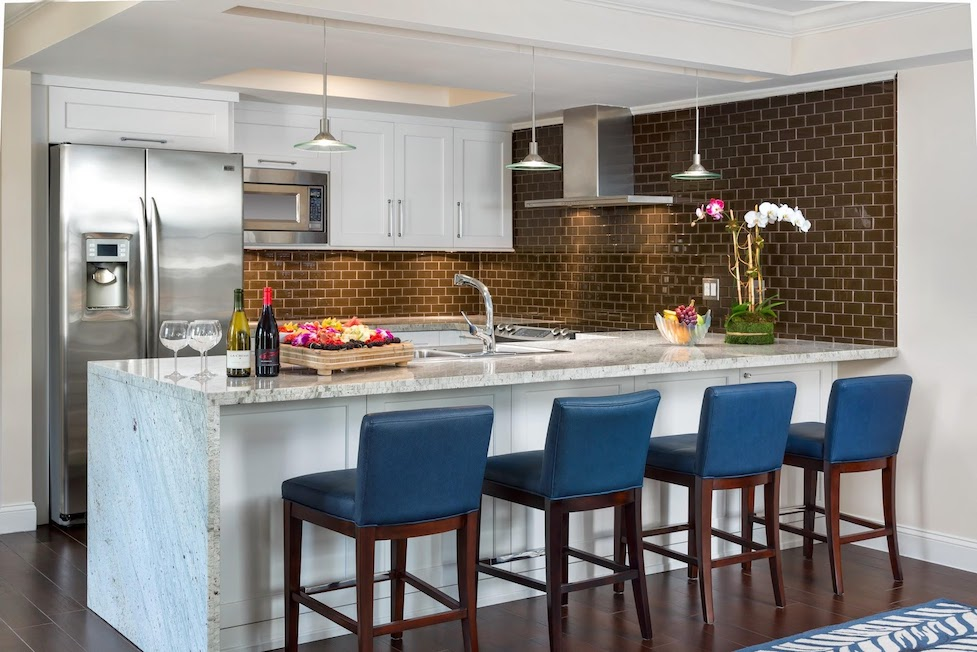 A modern and bright kitchen with an island and four navy blue bar stools