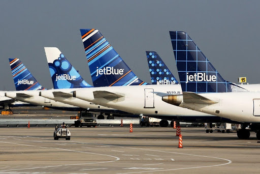 Five JetBlue airplanes lined up on the pavement