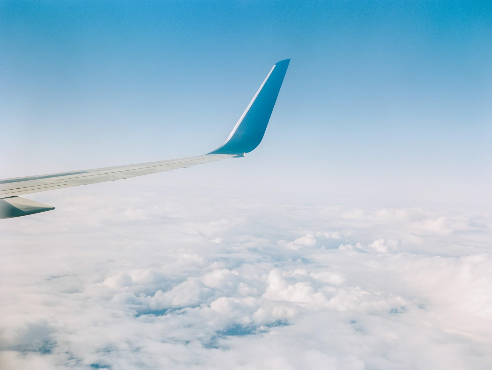An airplane wing in the clear blue sky surrounded by fluffy white clouds