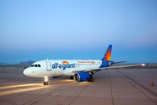 An Allegiant Airline airplane on the pavement at dusk getting ready for take off