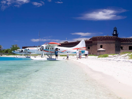 A small airplane on a beach with white sand and clear waters