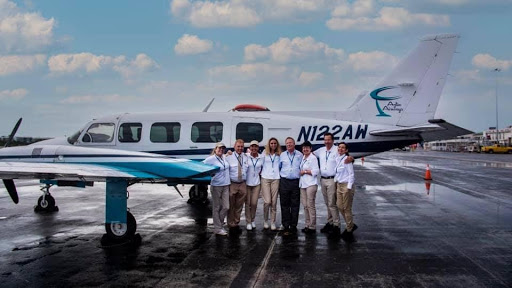 A group of staff posing in front of an airplane on the pavement.