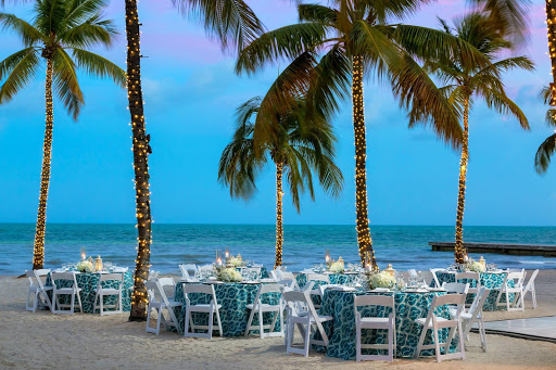 Dining set up at dusk on the beach surrounded by palm trees