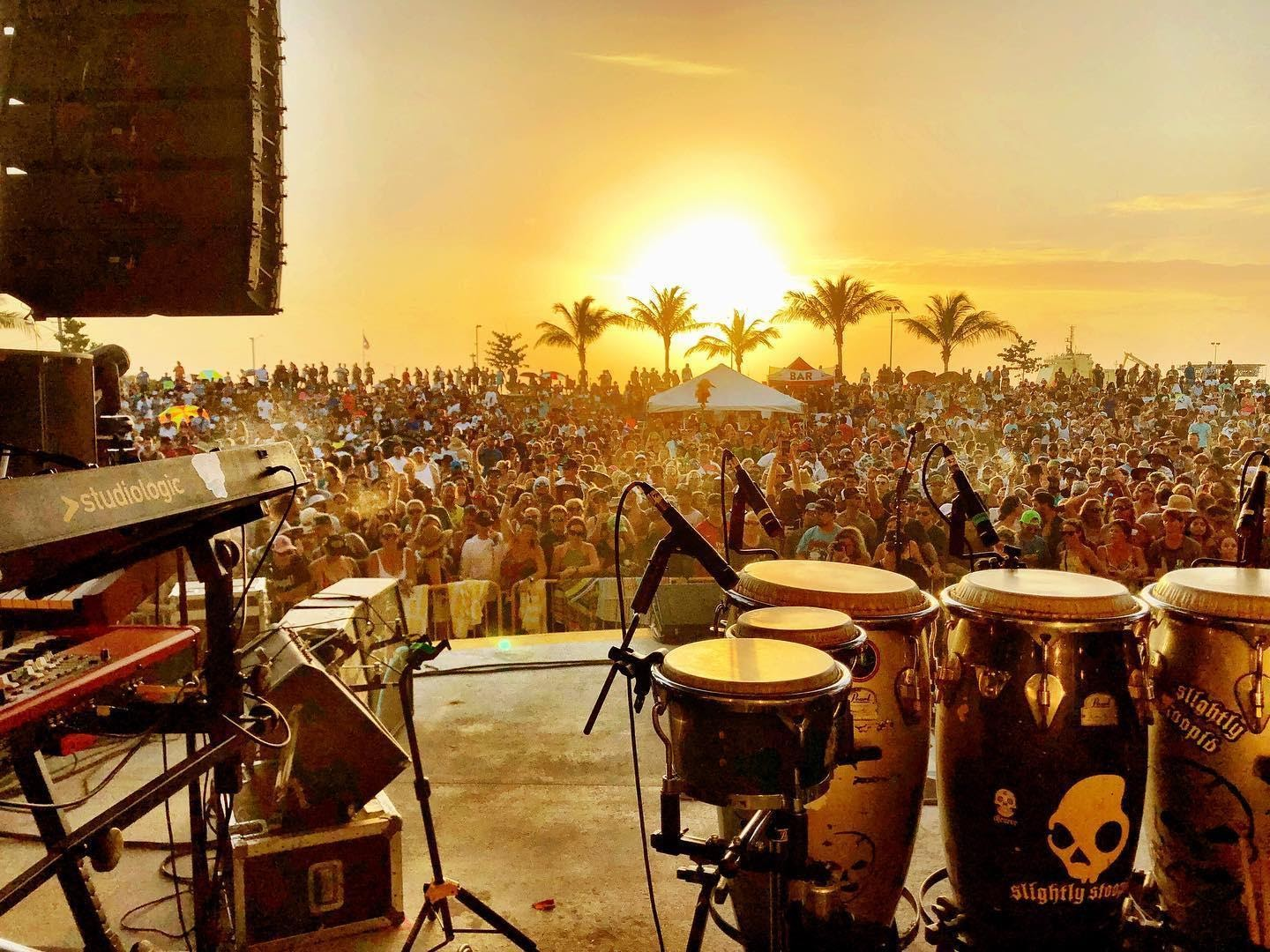 View of an outdoor concert packed with people at sunset