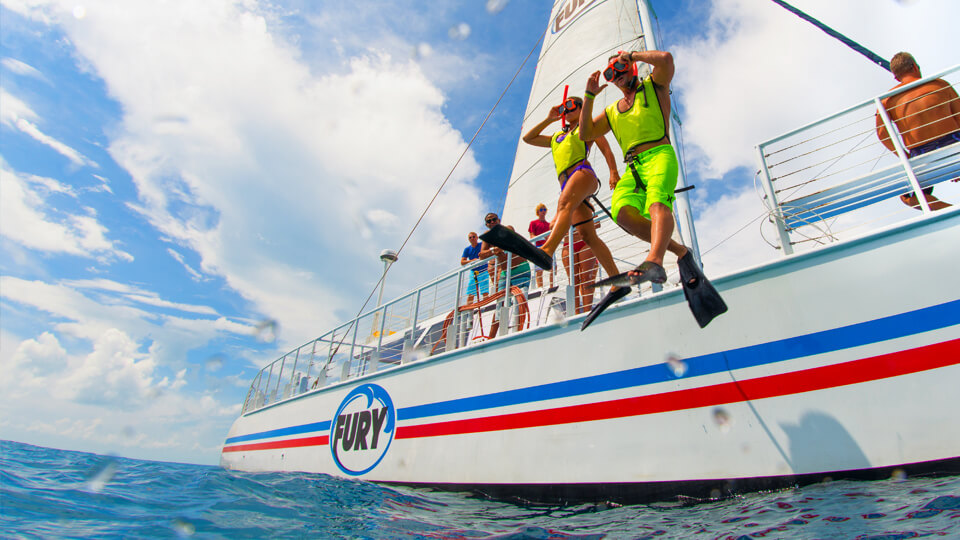 A man and a women jumping off a boat to go snorkeling